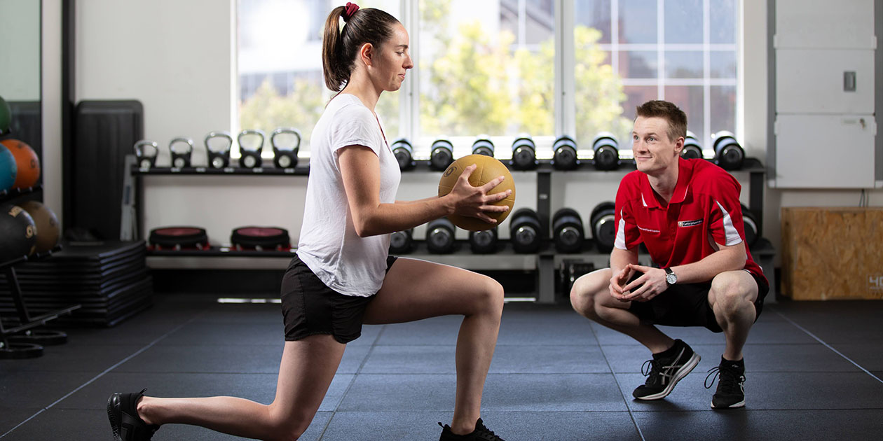 male student supervising female client doing exercise