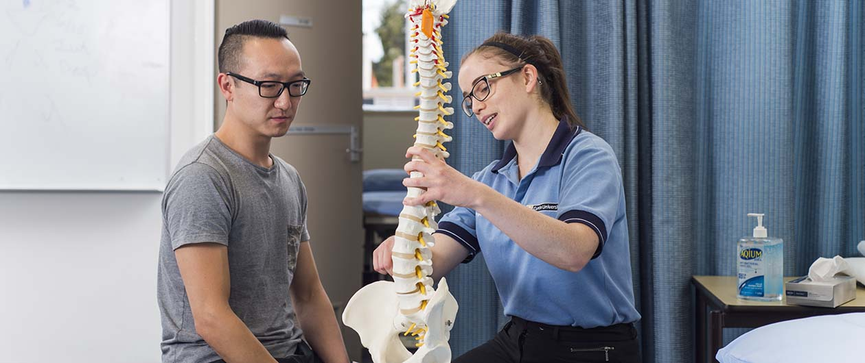 Physio student with client and model of skeleton