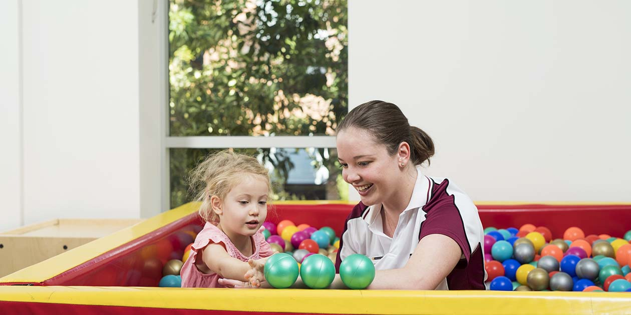 Occupational Therapy student in ball pit with a child