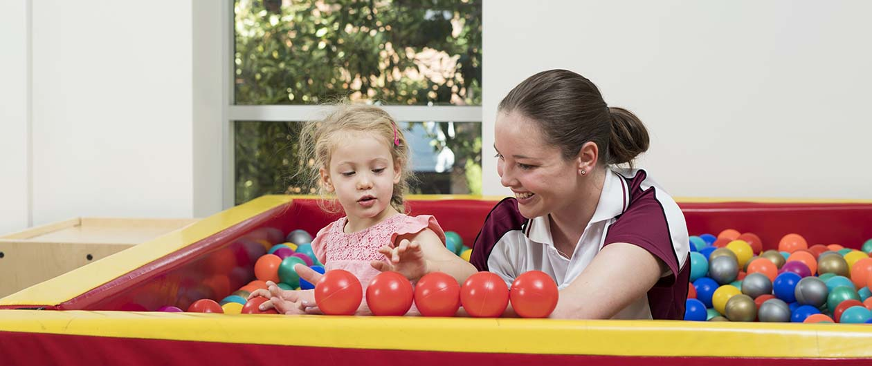 OT student in ball pit with child