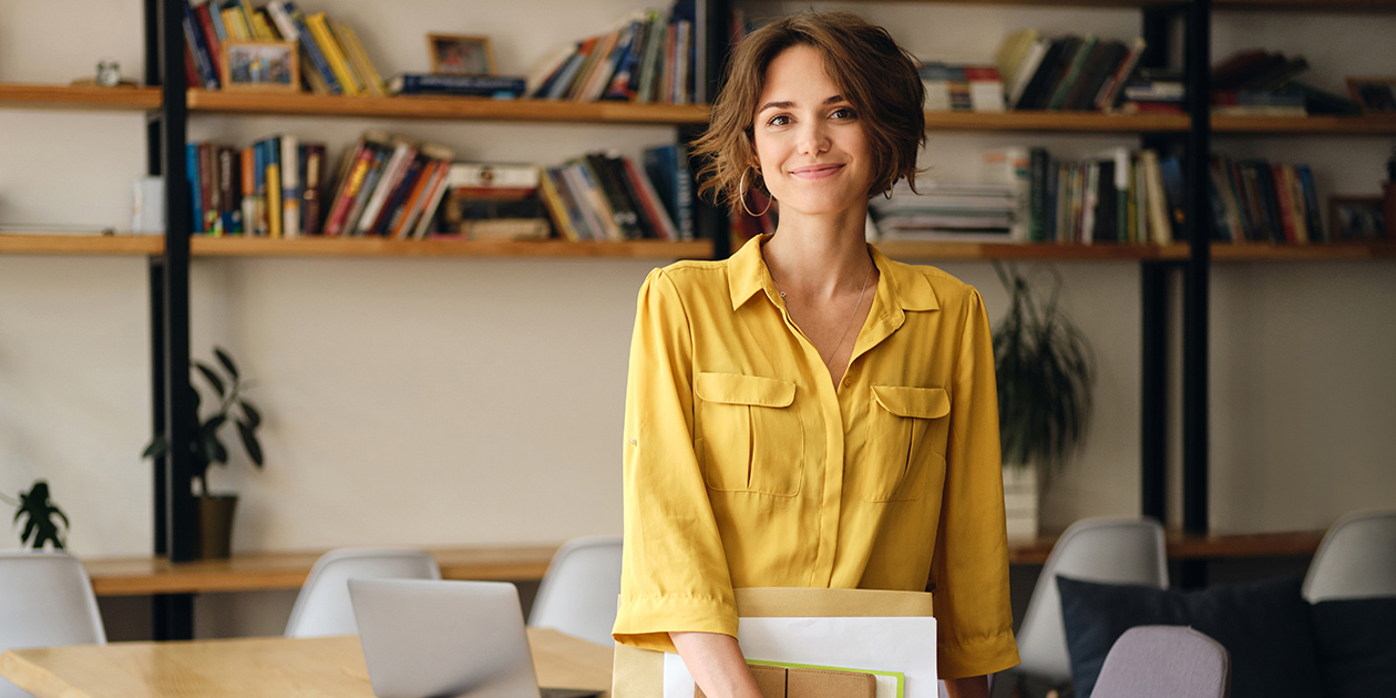 Business woman in a yellow top standing in an office
