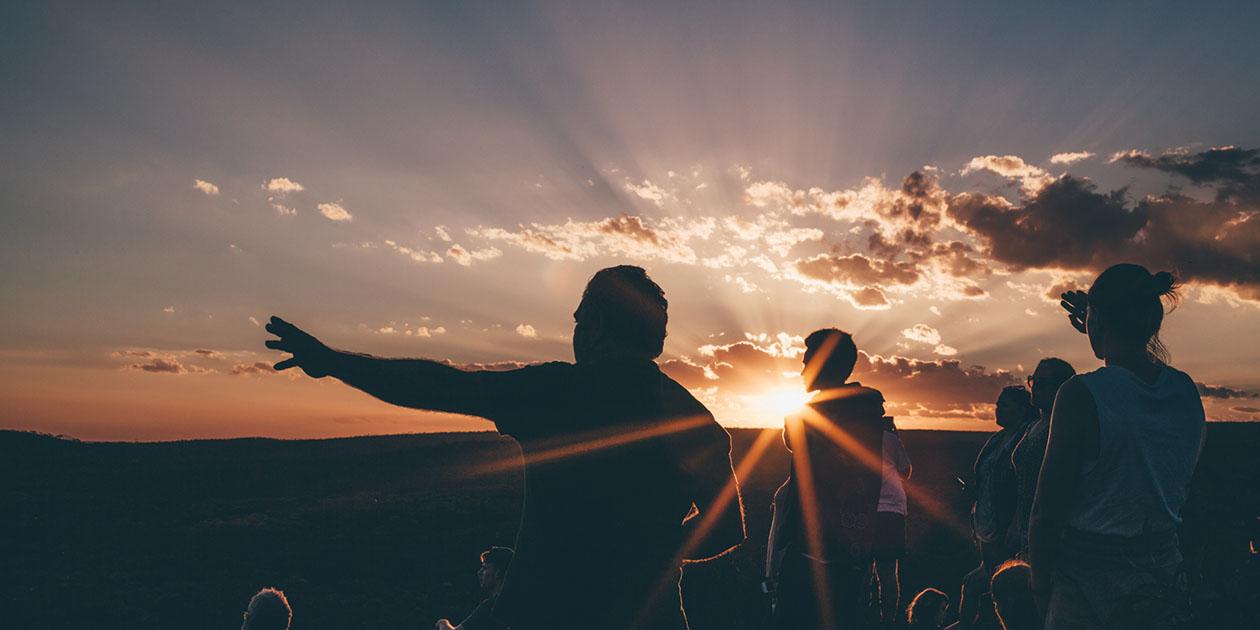 Man reaching at landscape at sunset