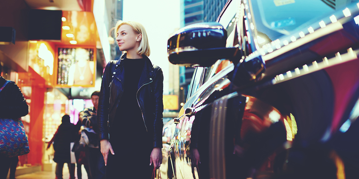 Young woman standing next to a car on the street