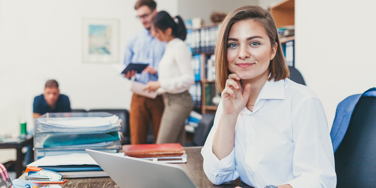 Young business woman working on a laptop in an office