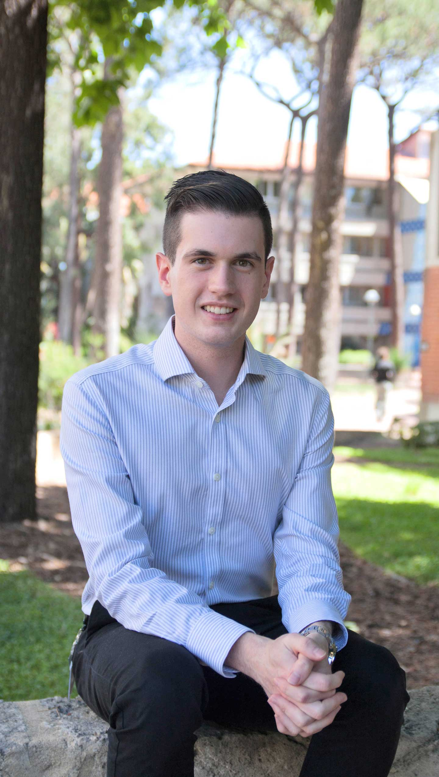Curtin Commerce student Christian Ford sitting on a brick wall against a background of trees and buildings