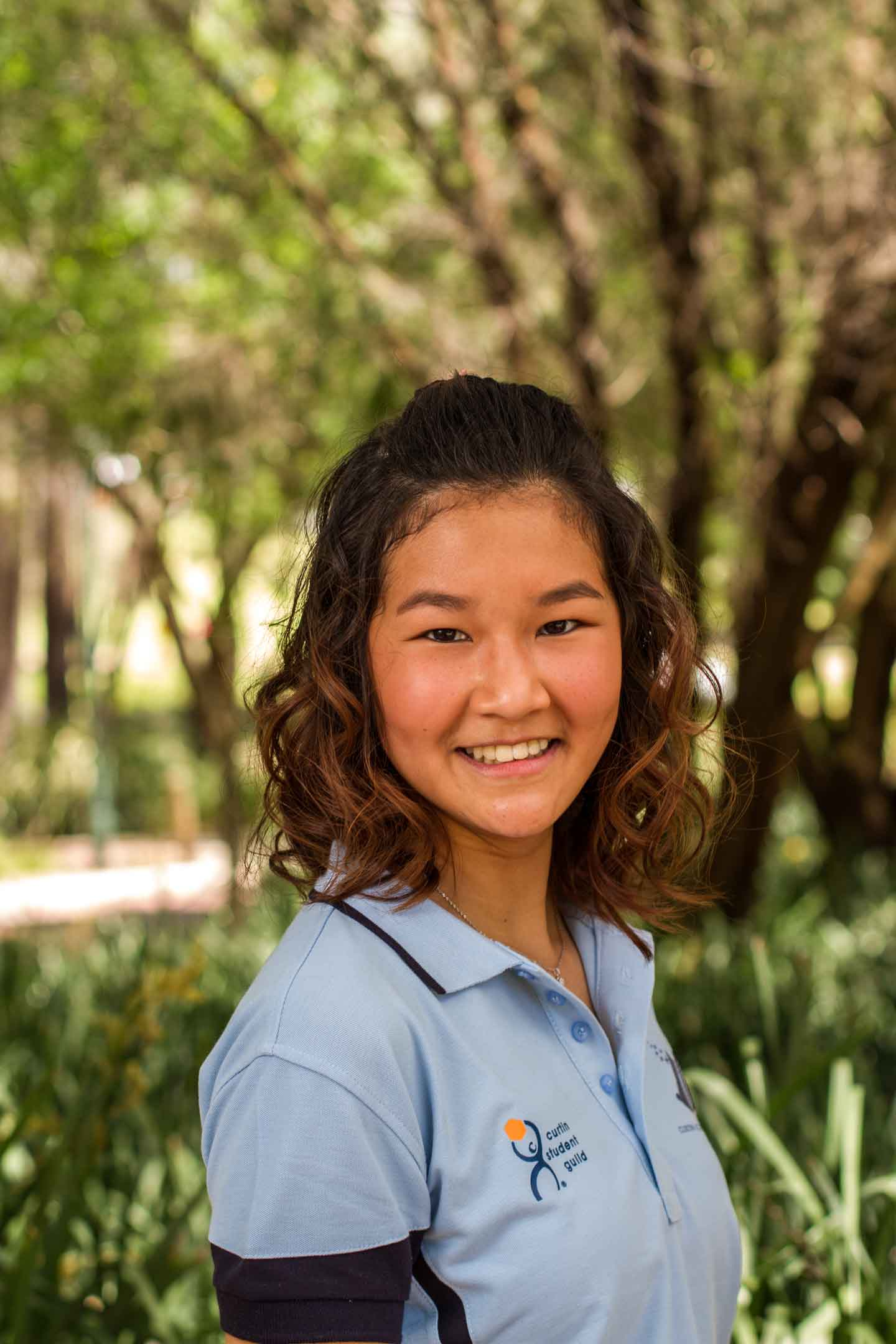 image of curtin student quincy lan in a blue polo shirt against green background