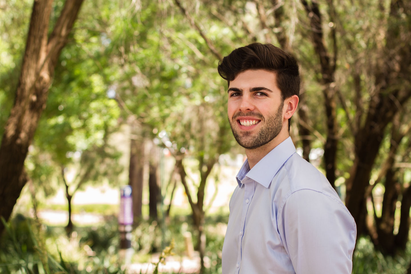 dark haired curtin student rob di giovanni standing against an out of focus background of green and brown trees