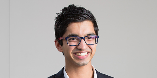 curtin student ryan soares wearing glasses and a suit standing against a dark green leafy background