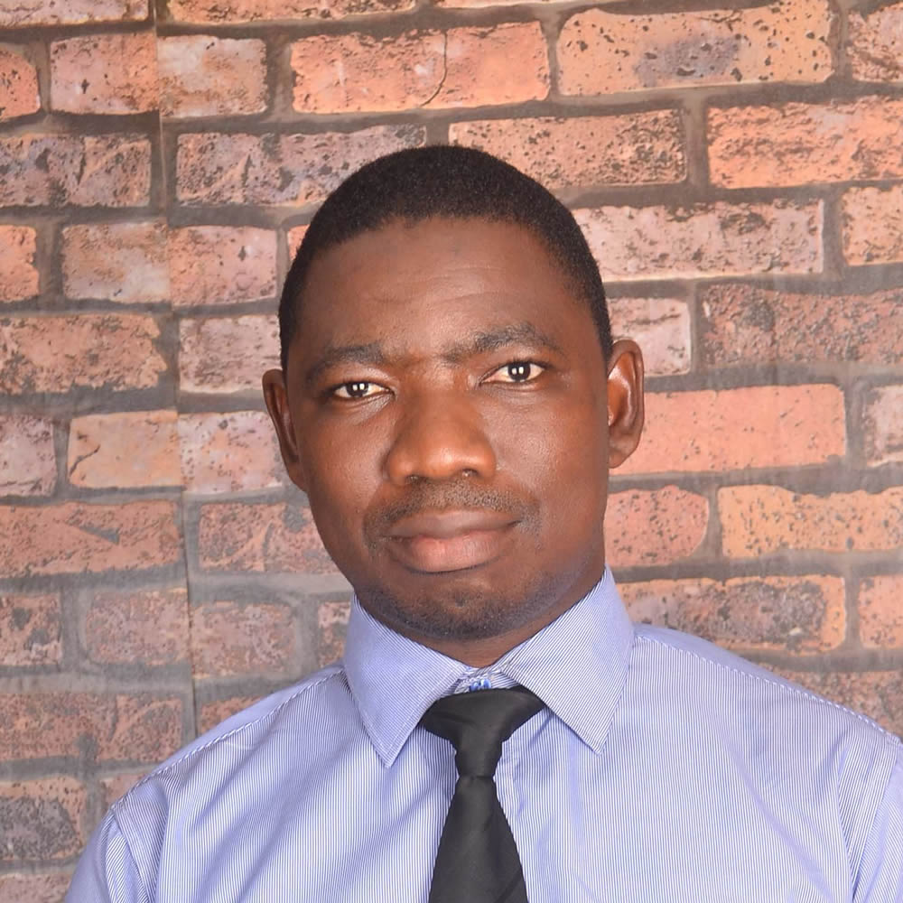 curtin student Emmanuel Adewuyi in a shirt and tie standing against a red brick background