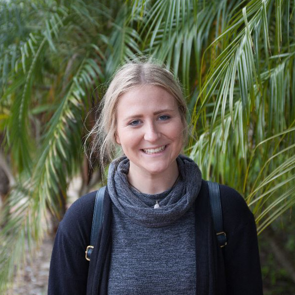 curtin student Emily Cousin standing against a backdrop of palm leaves and dressed in a dark coloured top and jacket