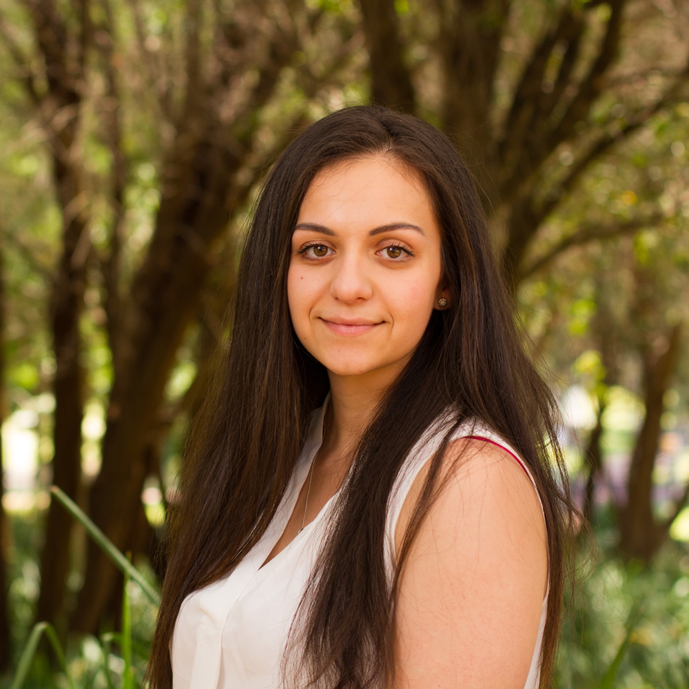 image of curtin student simone goncalves with long dark hair standing against an out of focus background of green and brown trees
